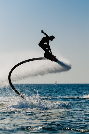jet skier: Silhouette of a hover board rider at sea