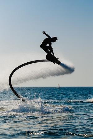hover: Silhouette of a hover board rider at sea