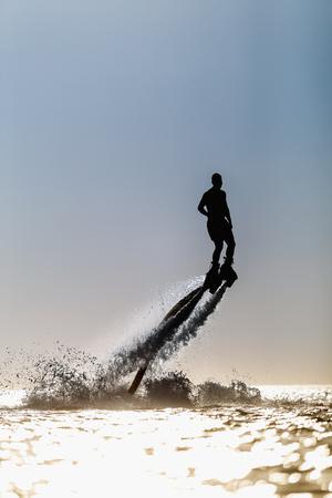 board: Silhouette of a fly board rider at sea