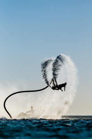 water skier: Silhouette of a fly board rider at sea