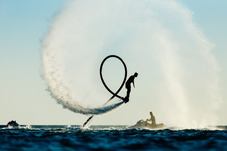 on the fly: Silhouette of a fly board rider at sea