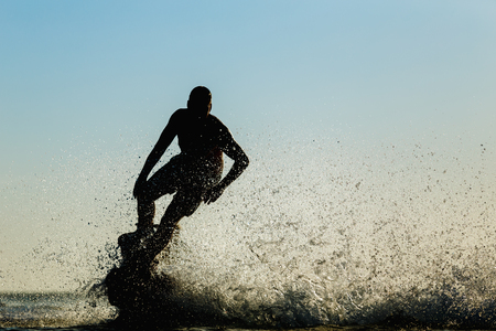 Silhouette of a fly board rider at sea