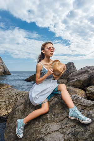 hot stone: Beautiful young teen girl in dress and hat posing on the stones in the sea fashion shoot at shore