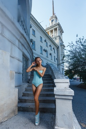 sensual girl: Beautiful young teen girl in bodysuit posing during city fashion shoot with classical building at background Stock Photo