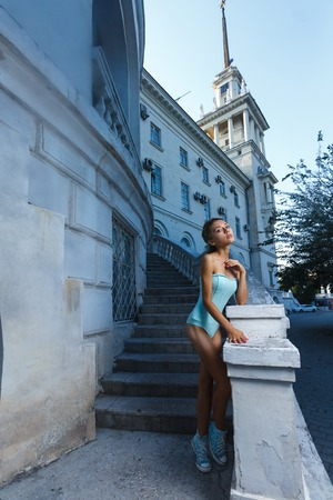 hot body: Beautiful young teen girl in bodysuit posing during city fashion shoot with classical building at background Stock Photo