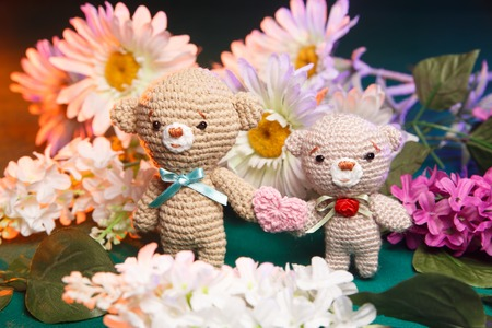 crocheted: Concept: love, relationship. Couple of knitted bears holding hands with flowers on background Stock Photo
