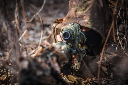 riffle: Sniper in camouflage suit with rifle in hand hide in the woods. Sniper aiming at target in forest, hero shoot Stock Photo
