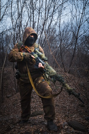 sniper training: Sniper in camouflage suit with rifle in hands walk in the wood, hero shot