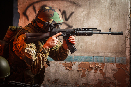 aiming: Soldier with the russian machine gun in abandoned building, hero shot.