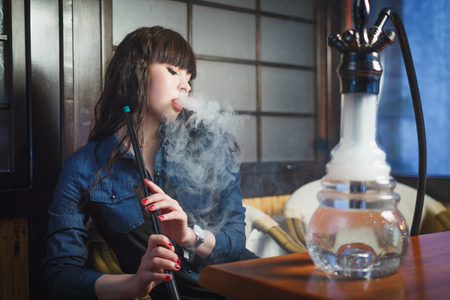 Concept: leisure lifestyle. Beautiful young woman with hookah in a bar restaurant Imagens