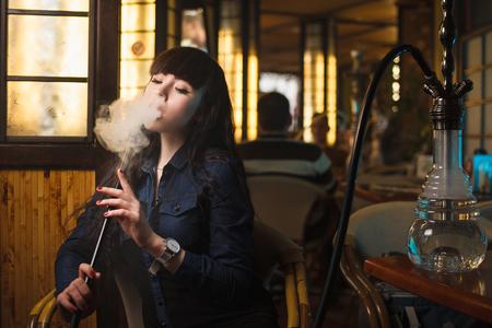 コンセプト: レジャー ・ ライフ スタイル。バーで水ギセルと美しい若い女性レストラン
