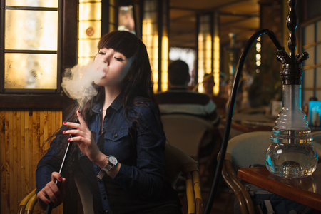 Concept: leisure lifestyle. Beautiful young woman with hookah in a bar restaurant Reklamní fotografie