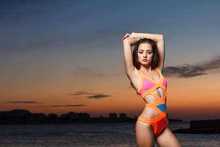 enjoing: Outdoor summer fashion lifestyle vacation portrait of hot sexy tanned beautiful girl in swimsuit enjoing herself at dramatic sunset Stock Photo