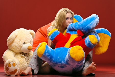 plush toys: A cute girl in pajamas sitting on a red beanbag chair with plush toys isolated on red background