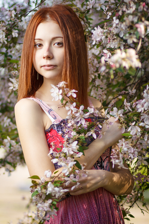 Beautiful redhead girl walking under the rays of the sunset in summer spring blooming forest