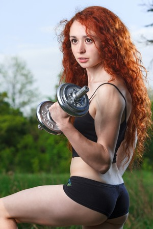 musculature: fitness, health, diet concept - stunning beautiful redhead girl with long curly hair and great musculature exercising with heavy dumbbells at summer spring forest Stock Photo