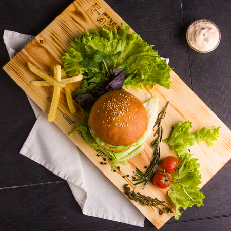 Concept: healthy food. Gourmet homemade burger with garnish and ingredients on the dark background.