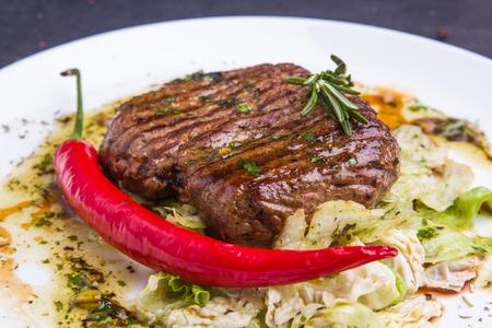 Konzept: gesunde Ernährung. Selbst gemachte gegrilltes Kalbssteak und Gemüse auf einer Platte mit Zutaten und Besteck um Standard-Bild