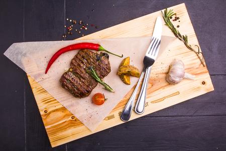 Konzept: gesunde Ernährung. Selbst gemachte gegrilltes Kalbssteak und Gemüse auf einem Holzbrett mit Zutaten und Besteck um