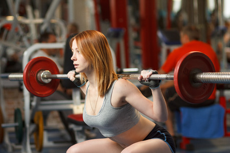 squats: Concept: sport, healthy lifestyle. Young strong girl do squats with a barbell