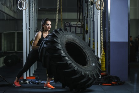 Concept: power, strength, healthy lifestyle, sport. Powerful attractive muscular woman CrossFit trainer doing giant tire workout at the gym Imagens