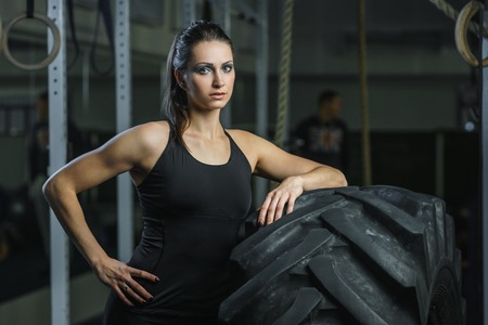 power giant: Concept: power, strength, healthy lifestyle, sport. Powerful attractive muscular woman CrossFit trainer doing giant tire workout at the gym Stock Photo