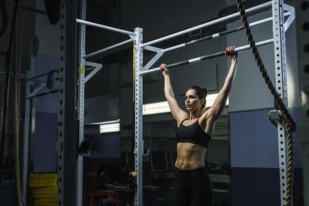 Concetto: potere, forza, stile di vita sano, sport. Potente donna muscolare attraente CrossFit trainer fare pull up durante l'allenamento in palestra