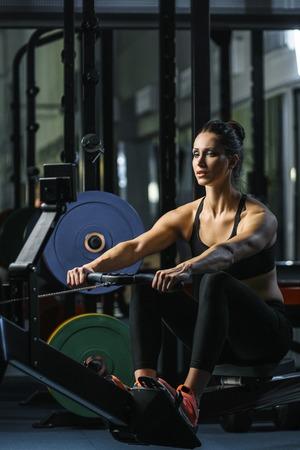 コンセプト: 力、強さ、健康的なライフ スタイル、スポーツ。強力な魅力的な筋肉女性 CrossFit トレーナー ジムで屋内の漕ぎ手の運動を行う 写真素材