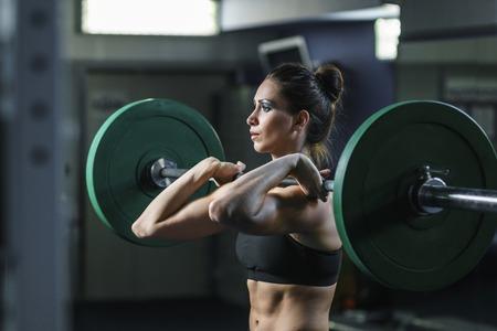Concept: macht, kracht, gezonde levensstijl, sport. Krachtige aantrekkelijke gespierde vrouw CrossFit trainer doen training met halter in de sportschool
