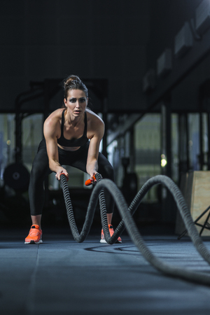 Concepto: el poder, la fuerza, la vida sana, el deporte. Potente atractiva mujer muscular entrenador CrossFit hacer entrenamiento de combate con cuerdas en el gimnasio Foto de archivo - 62794758