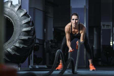 Concept: macht, kracht, gezonde levensstijl, sport. Krachtige aantrekkelijke gespierde vrouw CrossFit trainer gaan de strijd training met touwen in de sportschool Stockfoto