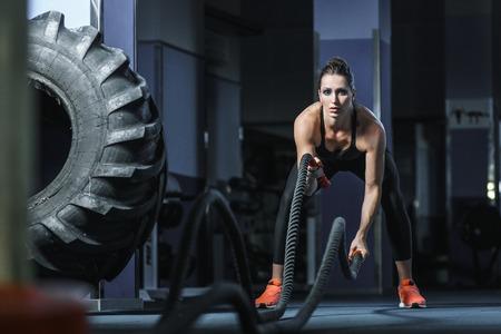 Konzept: Kraft, Stärke, gesunde Lebensweise, Sport. Leistungsstarke attraktive muskulösen Frau CrossFit Trainer kämpfen Training mit Seilen in der Turnhalle Standard-Bild - 62794763