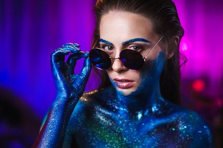 Portrait of an beautiful woman painted with purple cosmic colors and spangled. Body art project. Concept: fashion, makeup, extraordinary. Stock Photo