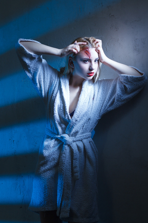 Concept: victim, accident, domestic violence. Beautiful young woman in bathrobe suffer head trauma in dramatic light. Stock Photo