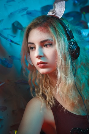Concept: deadly music, sound kills. Beautiful young woman in headphones with bloody parts of cd sticking out of her head. Accident murder victim. Undead.