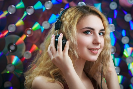 Concept: hipster lifestyle, relaxation. Beautiful young woman in headphones have fun and listen music with colorful CDs on background.