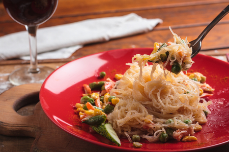 Concept: restaurant menus, healthy eating, homemade, gourmands, gluttony. Rice noodles with green beans and vegetables on a messy weathered wooden background.
