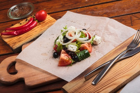 gluttony: Concept: restaurant menus, healthy eating, homemade, gourmands, gluttony. Greek salad served on paper with ingredients on weathered wooden background.