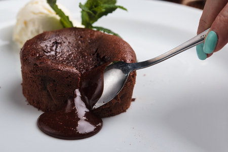 gluttony: Concept: restaurant menus, healthy eating, homemade, gourmands, gluttony. White plate with chocolate fondant and ice cream on a messy vintage wooden background. Stock Photo