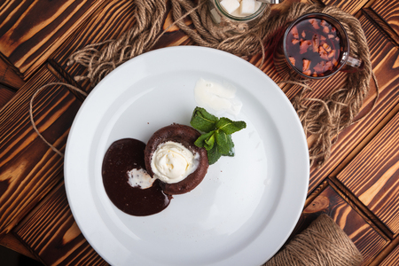gluttony: Concept: restaurant menus, healthy eating, homemade, gourmands, gluttony. White plate with chocolate fondant and ice cream on a messy vintage wooden background. Top-down view. Stock Photo