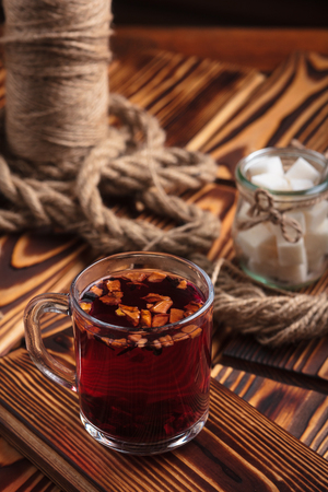 Concept: restaurant menus, healthy eating, homemade, gourmands, gluttony. Hibiscus tea with fruit pieces and sugar in glass jar on vintage wooden background. Stock Photo
