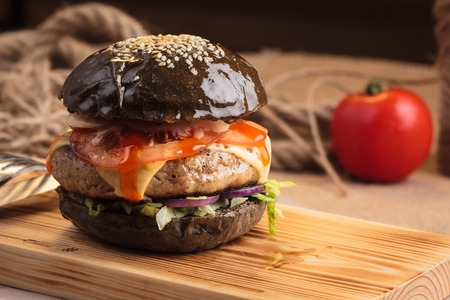 Concept: restaurant menus, healthy eating, homemade, gourmands, gluttony. Trendy glossy burger with beef in black bun with ingredients on messy vintage wooden background.