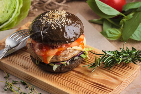 gluttony: Concept: restaurant menus, healthy eating, homemade, gourmands, gluttony. Trendy glossy burger with beef in black bun with ingredients on messy vintage wooden background.