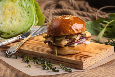 gluttony: Concept: restaurant menus, healthy eating, homemade, gourmands, gluttony. Trendy glossy burger with chicken with ingredients on messy vintage wooden background.