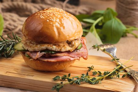 Concept: restaurant menus, healthy eating, homemade, gourmands, gluttony. Trendy glossy breakfast burger with ham and eggs with ingredients on messy vintage wooden background. Stock Photo