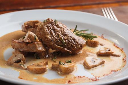 Concepto: menús de restaurantes, la alimentación saludable, hecho en casa, gourmands, la gula. Placa blanca de medallones de cerdo con salsa de setas en mesa de madera desgastada. Foto de archivo