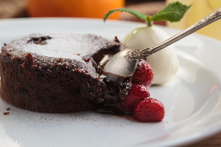 Concept: restaurant menus, healthy eating, homemade, gourmands, gluttony. White plate with chocolate fondant with strawberry and ice cream on a messy vintage wooden background.