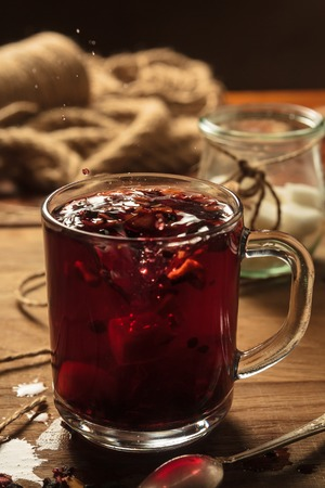 Concept: restaurant menus, healthy eating, homemade, gourmands, gluttony. Hibiscus tea with fruit pieces and sugar in glass on vintage wooden background. Stock Photo