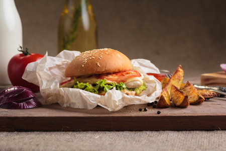 gluttony: Concept: restaurant menus, healthy eating, homemade, gourmands, gluttony. Classic burger with chicken with ingredients and potato wedges on messy vintage wooden background. Stock Photo