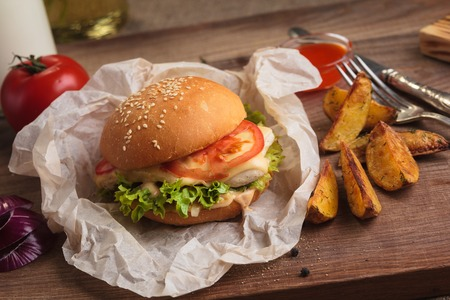 Concept: restaurant menus, healthy eating, homemade, gourmands, gluttony. Classic burger with chicken with ingredients and potato wedges on messy vintage wooden background. Stock Photo